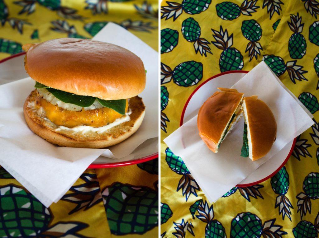 Na talerzu hamburger na tle żółtej tkaniny w zielone ananasy.