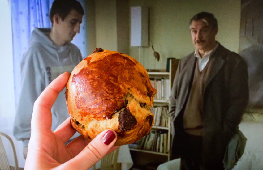 """Kadr z filmu """"Dzień świra"""", na jego tle brioszka czekoladowa."""
