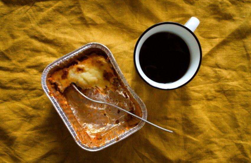 Na żółtym tle gotowa lazania, obok kubek z czarną kawą.